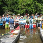 Whole group in water with canoes